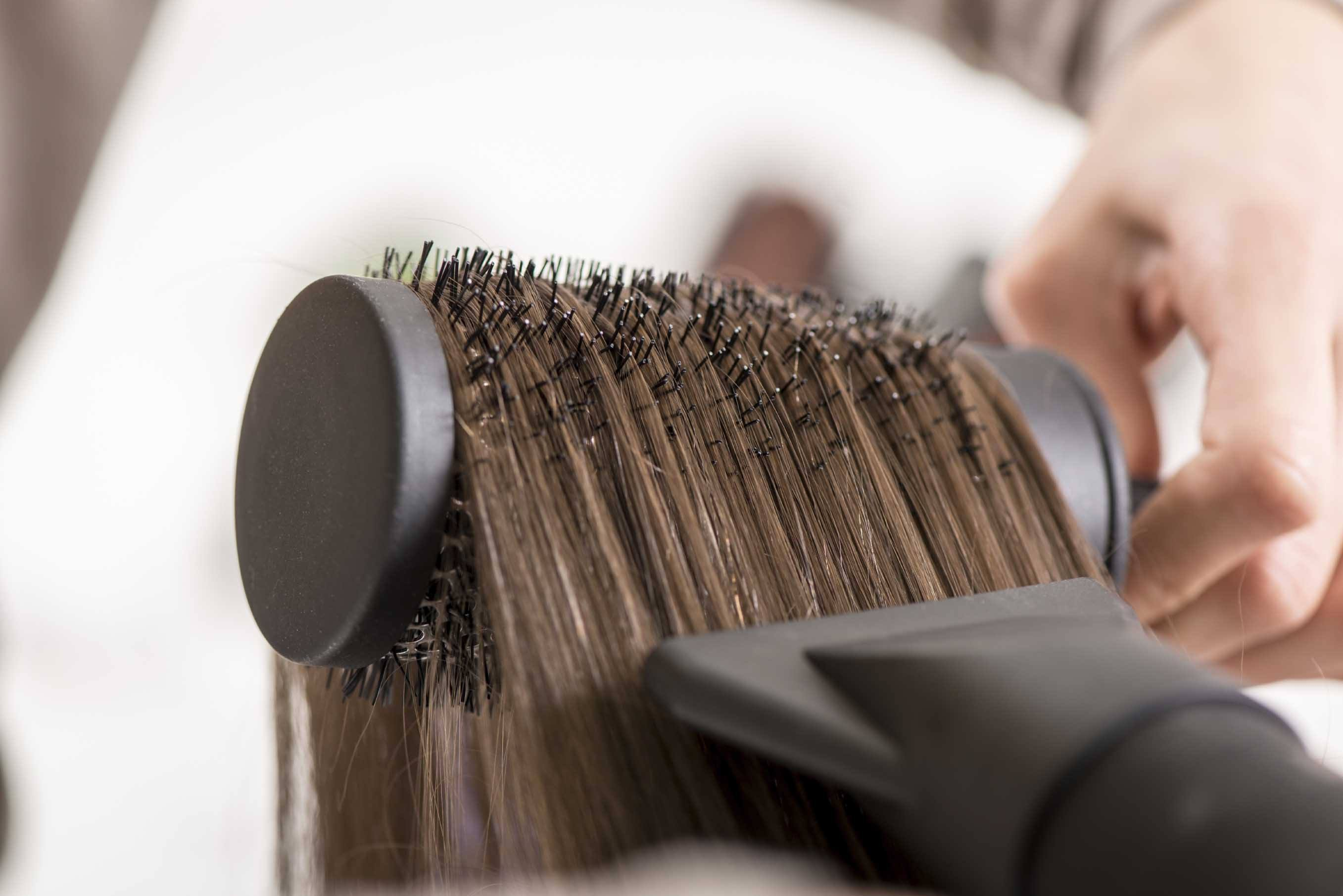 Close-up of a drying brown hair with hair dryer and round brush