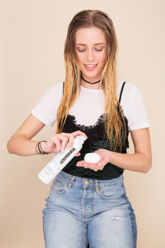 crimped hair tutorial: Blonde model with long damp hair applying mousse