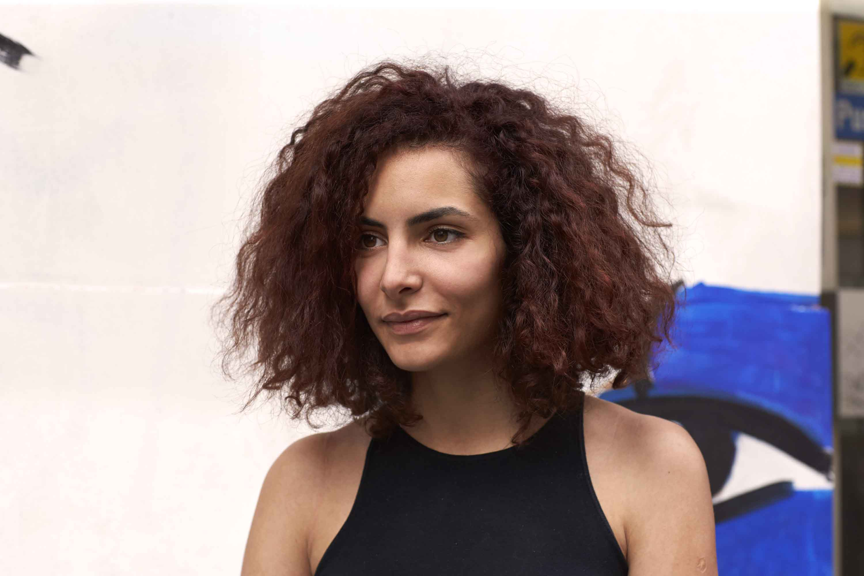 Medium hairstyles for thick hair: Street style shot of a woman with mid-length red brown naturally curly hair, wearing a black top