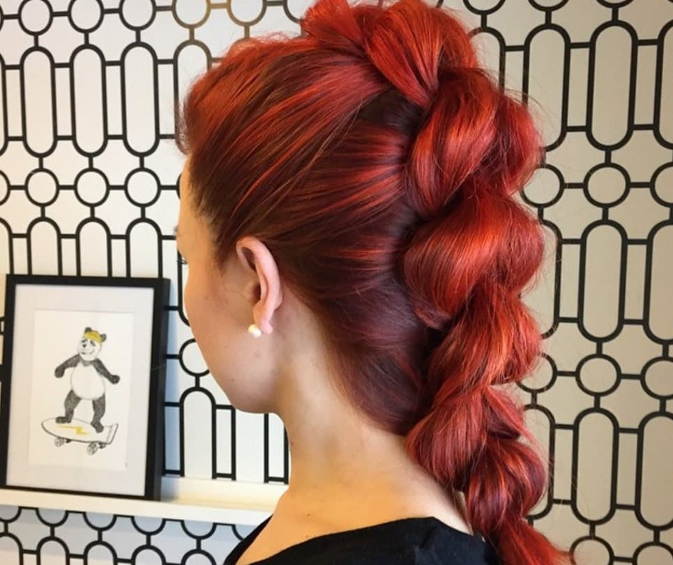 back view image of a woman with bright red bold hair in a French braid faux hawk