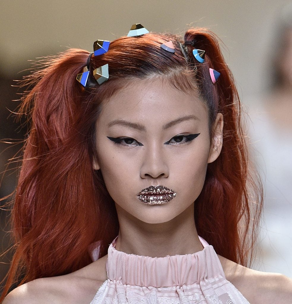 model on the Fendi SS17 runway with dyed red hair worn in pigtails with candy look accessories attached and glitter lips