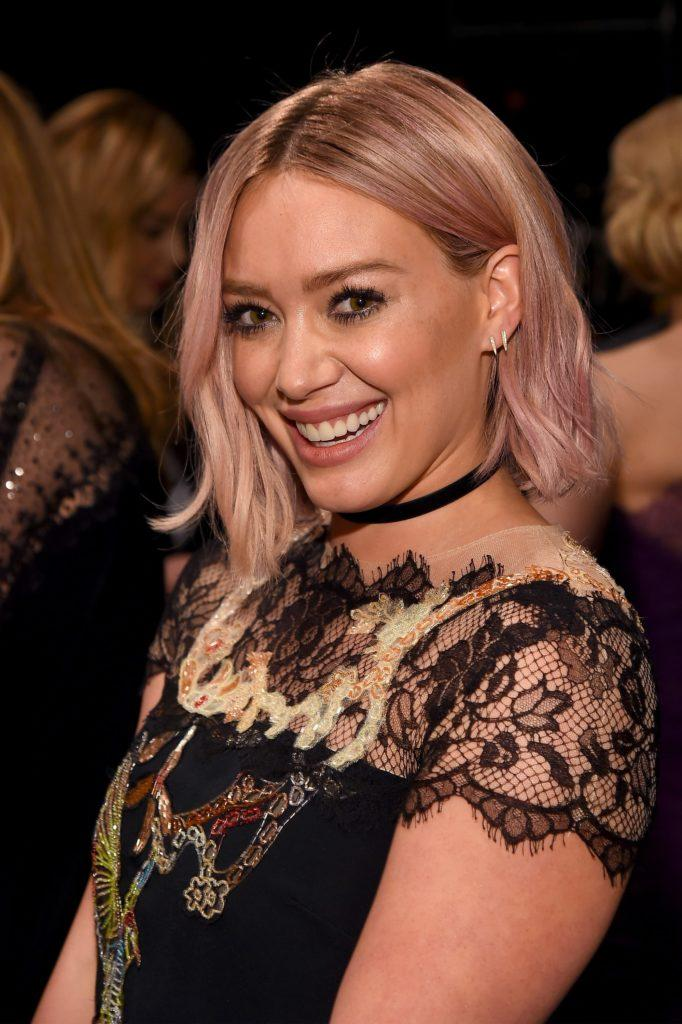 hilary duff with pink hair styled into a long bob and waves wearing a lace dress
