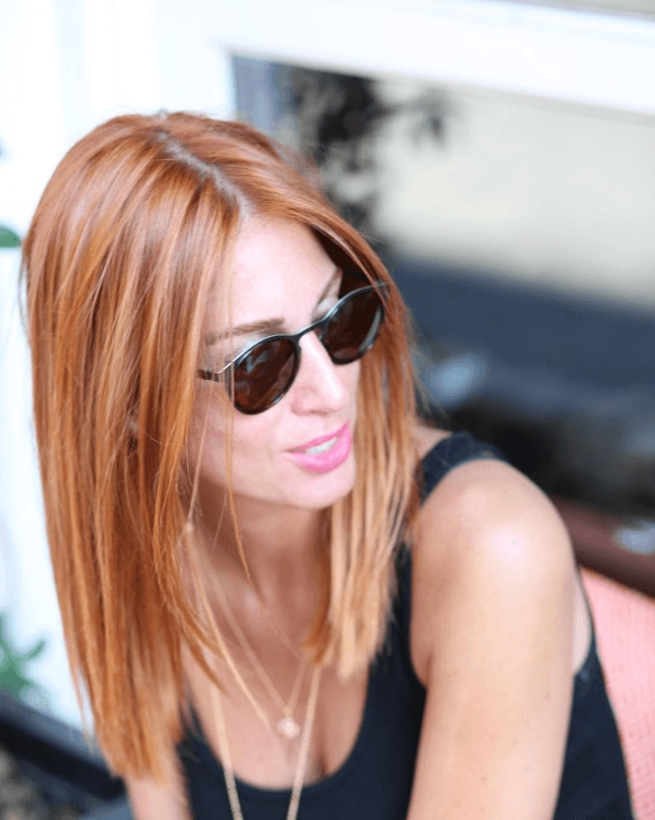 side view of a woman with reddish hair worn straight, wearing sunglasses and a black dress