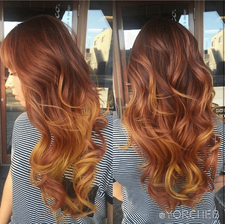 side view of a woman with long wavy hair worn in a an orange ombre