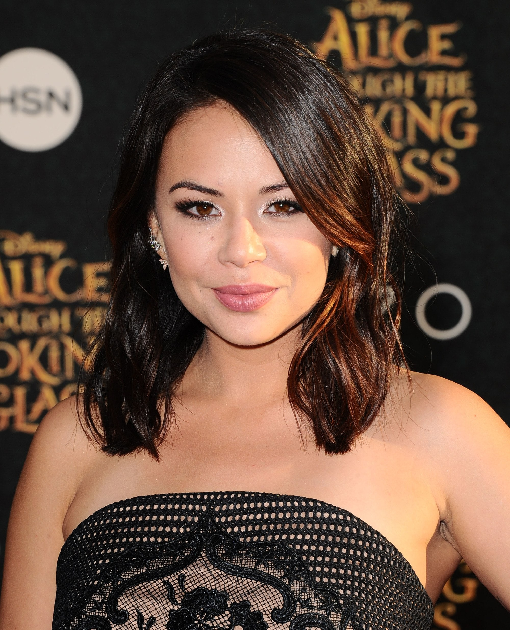 Medium hairstyles for thick hair: Janel Parrish with her dark brown hair in a glossy medium length cut with a sweeping side fringe
