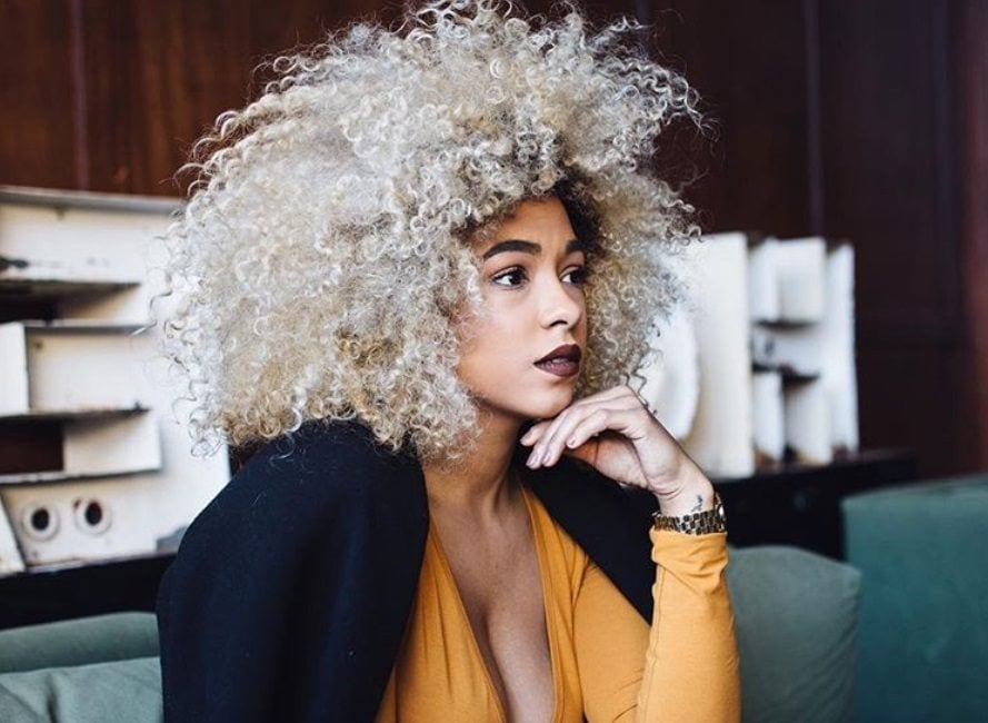 close up shot of woman with blonde afro curls, wearing black jacket and yellow top