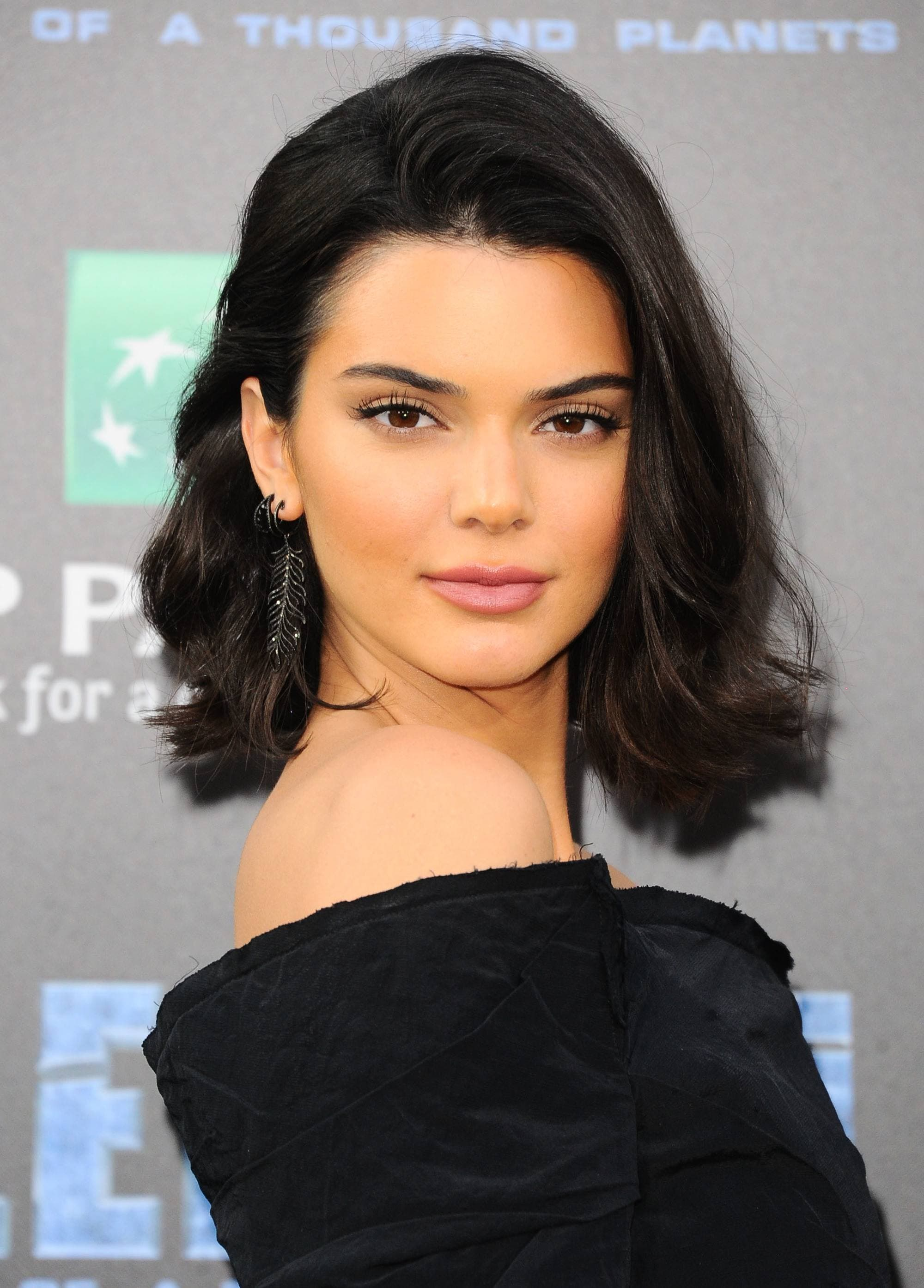 Medium hairstyles for thick hair: Kendall Jenner with dark brown long bob length hair with flicked-out layers, wearing an off shoulder black dress
