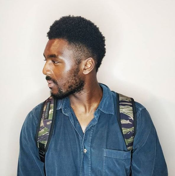 A young black man turning to the side with a South of France hairstyle