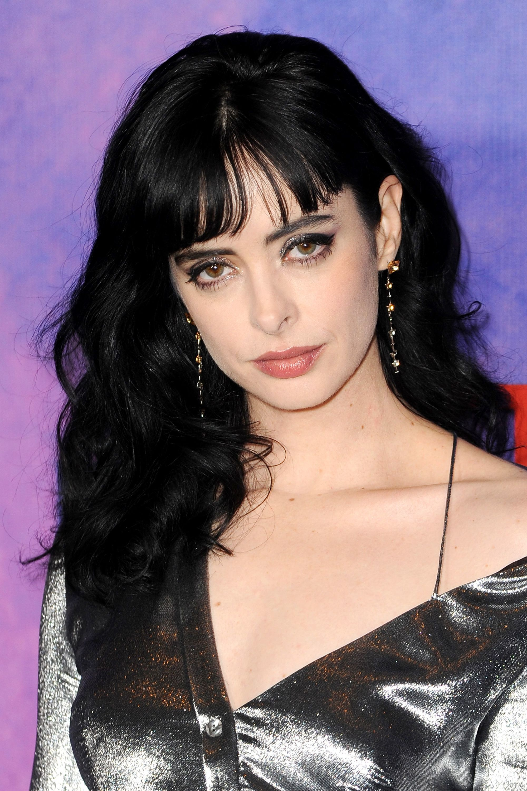Medium hairstyles for thick hair: Krysten Ritter with mid-length dark brown wavy hair with bangs
