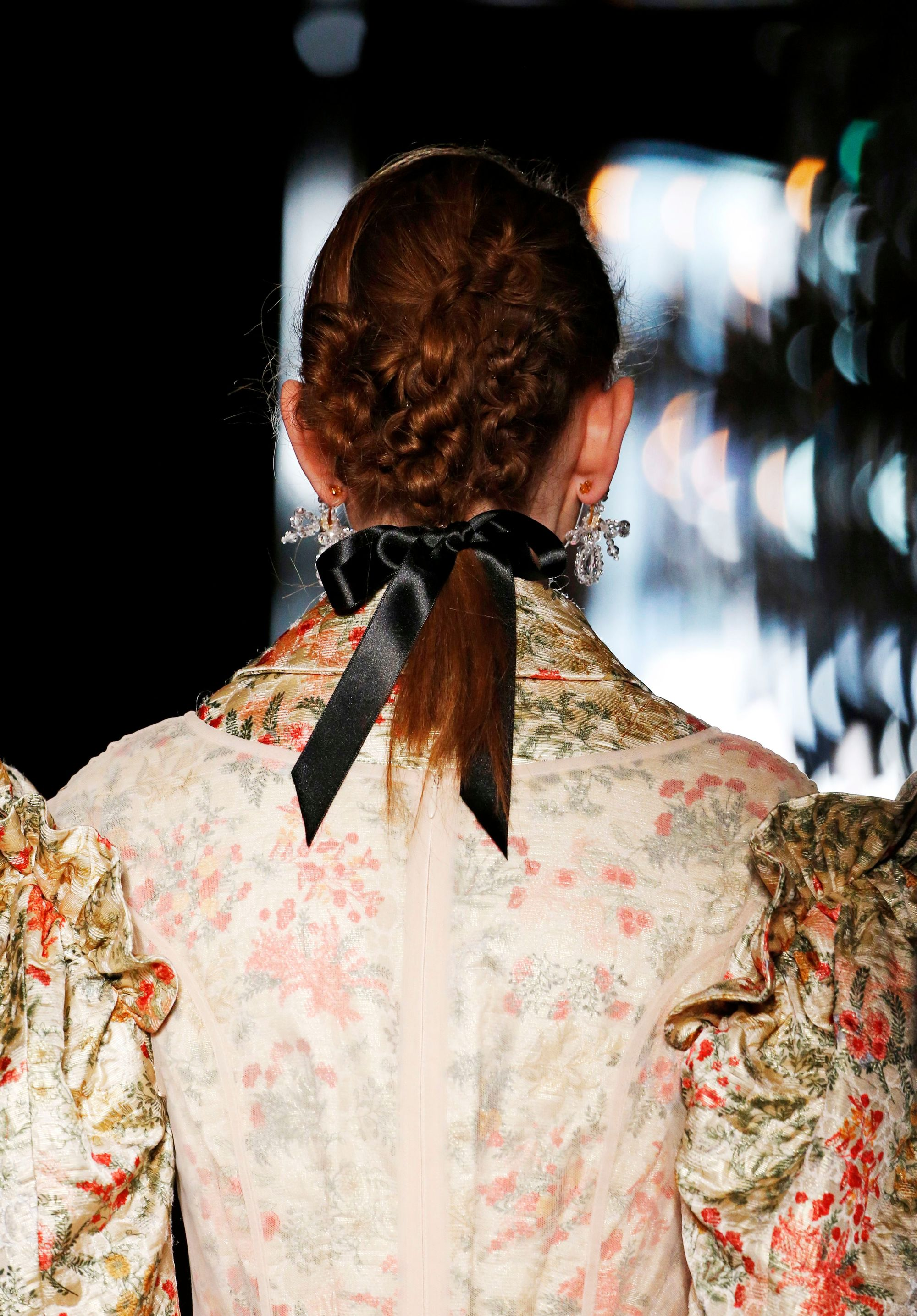 back view of redhead model with intricate braided style with black satin ribbon bow finish wearing cream pattern dress