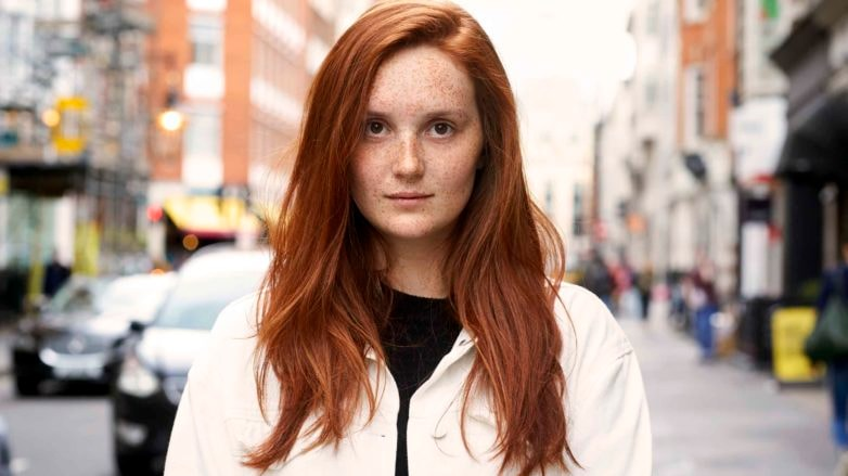 Red hair: Woman on the street with long pumpkin spice hair with side parting wearing a white jacket over a black top.