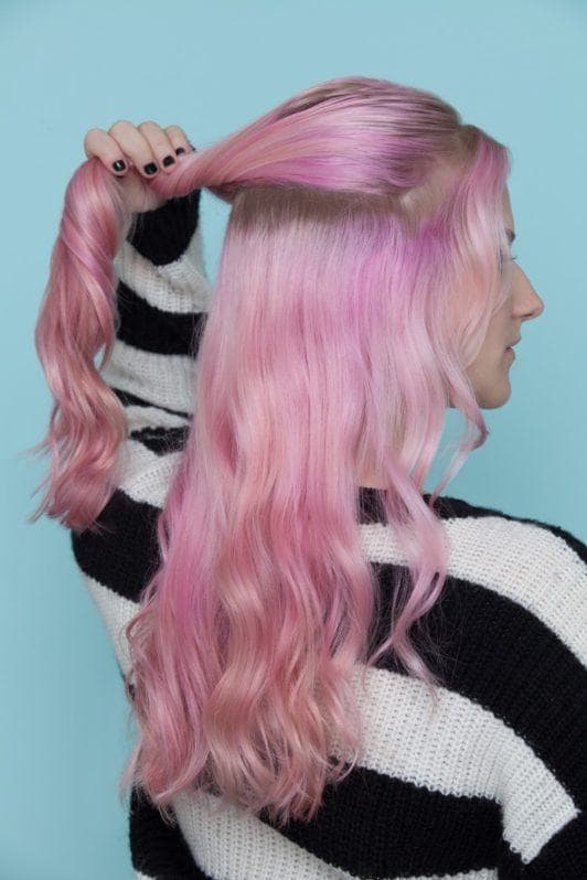 a woman lifting up her wavy pink hair