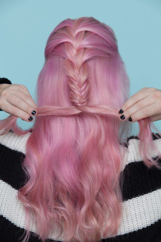 girl with pink hair weaves a fishtail braid in her hair