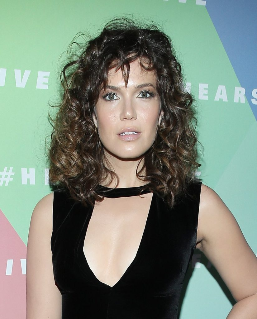 Mandy Moore on the red carpet with an '80s Flashdance-inspired perm hairstyle in a black dress