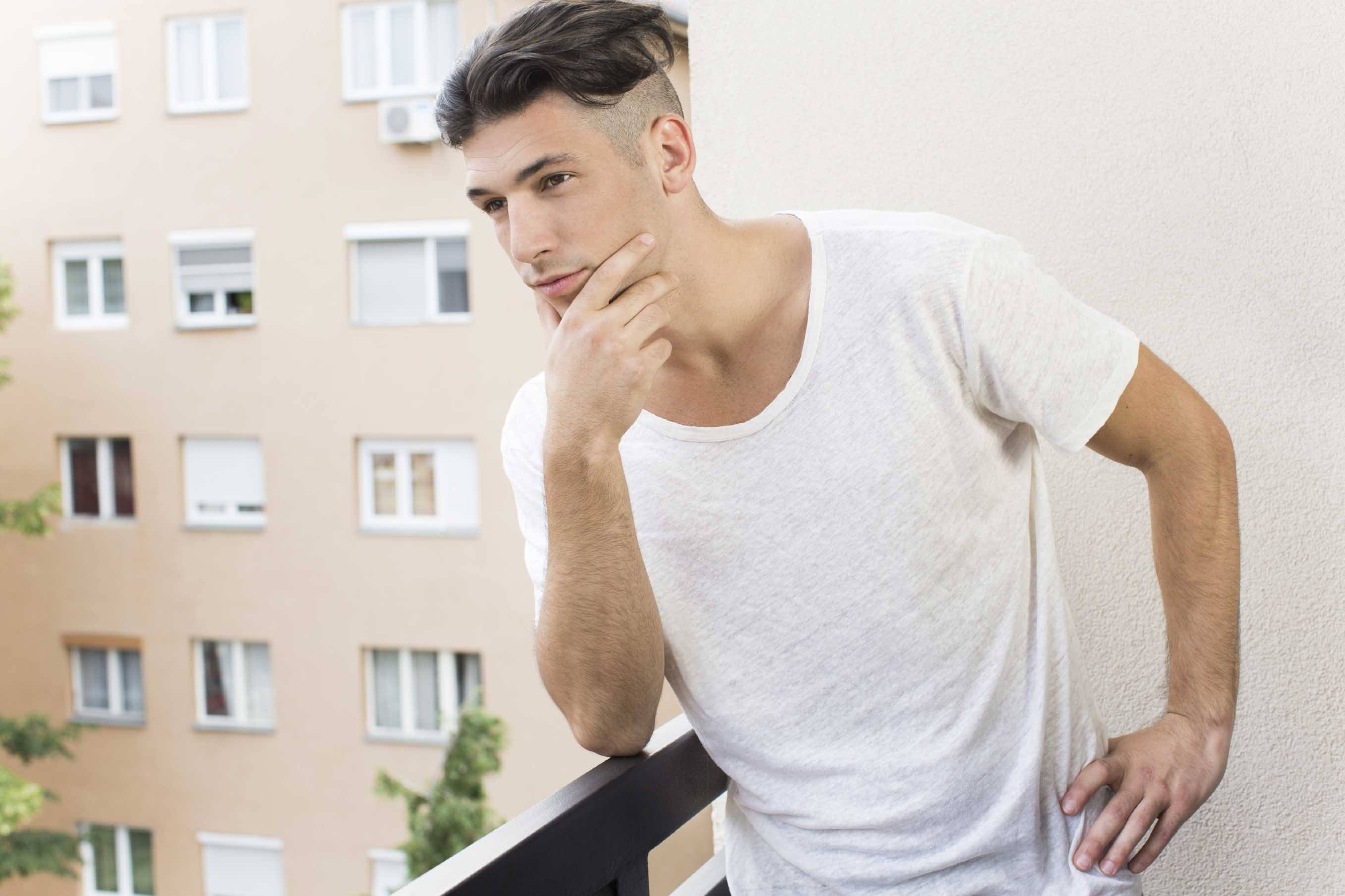 Men's haircuts for round faces: A man with a dark pompadour and undercut hairstyle, wearing white shirt and posing outside