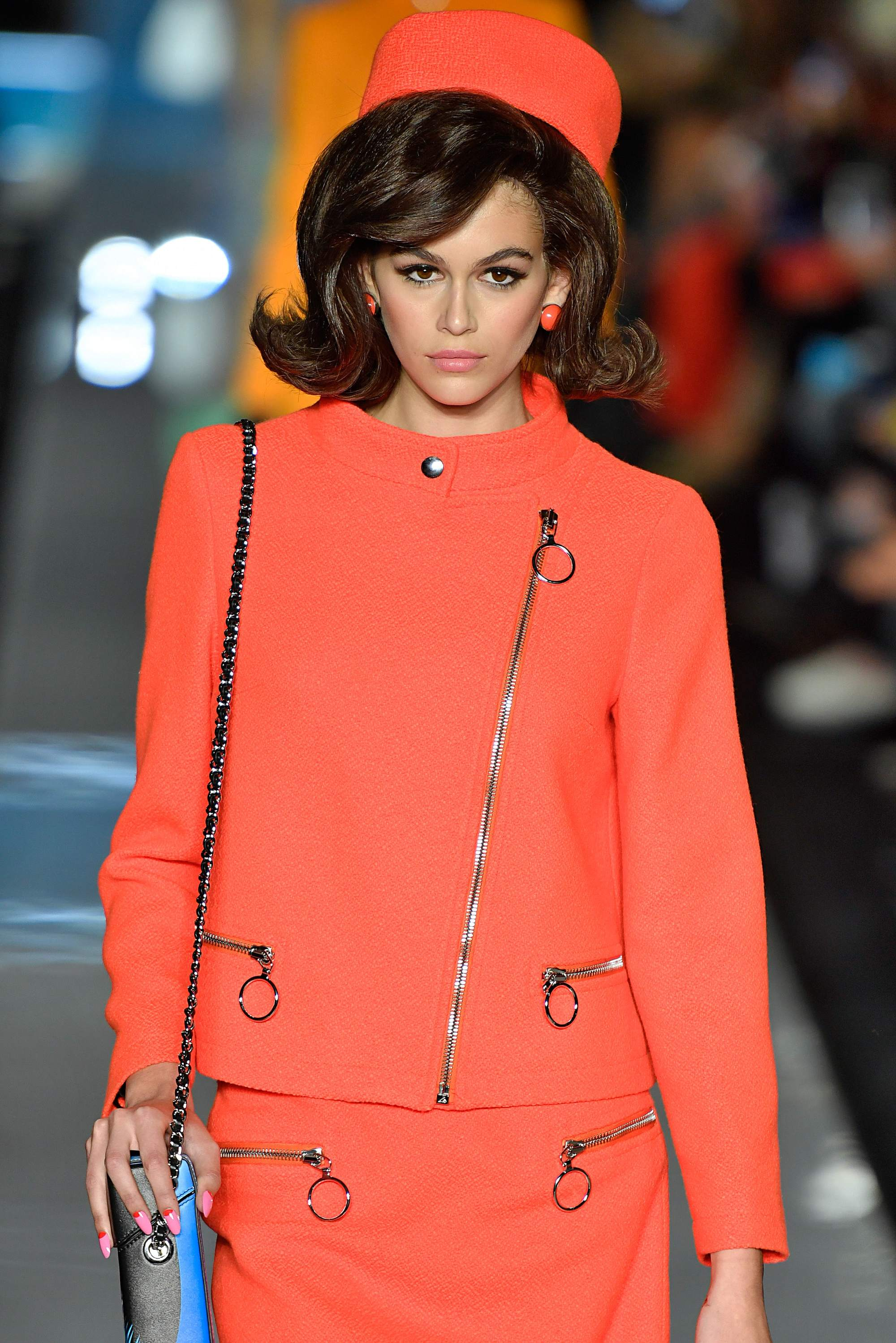 kaia gerber at moschino runway show with flicked out dark brown shoulder length bob and sweeping side fringe wearing bold coral coloured suit and pillbox hat