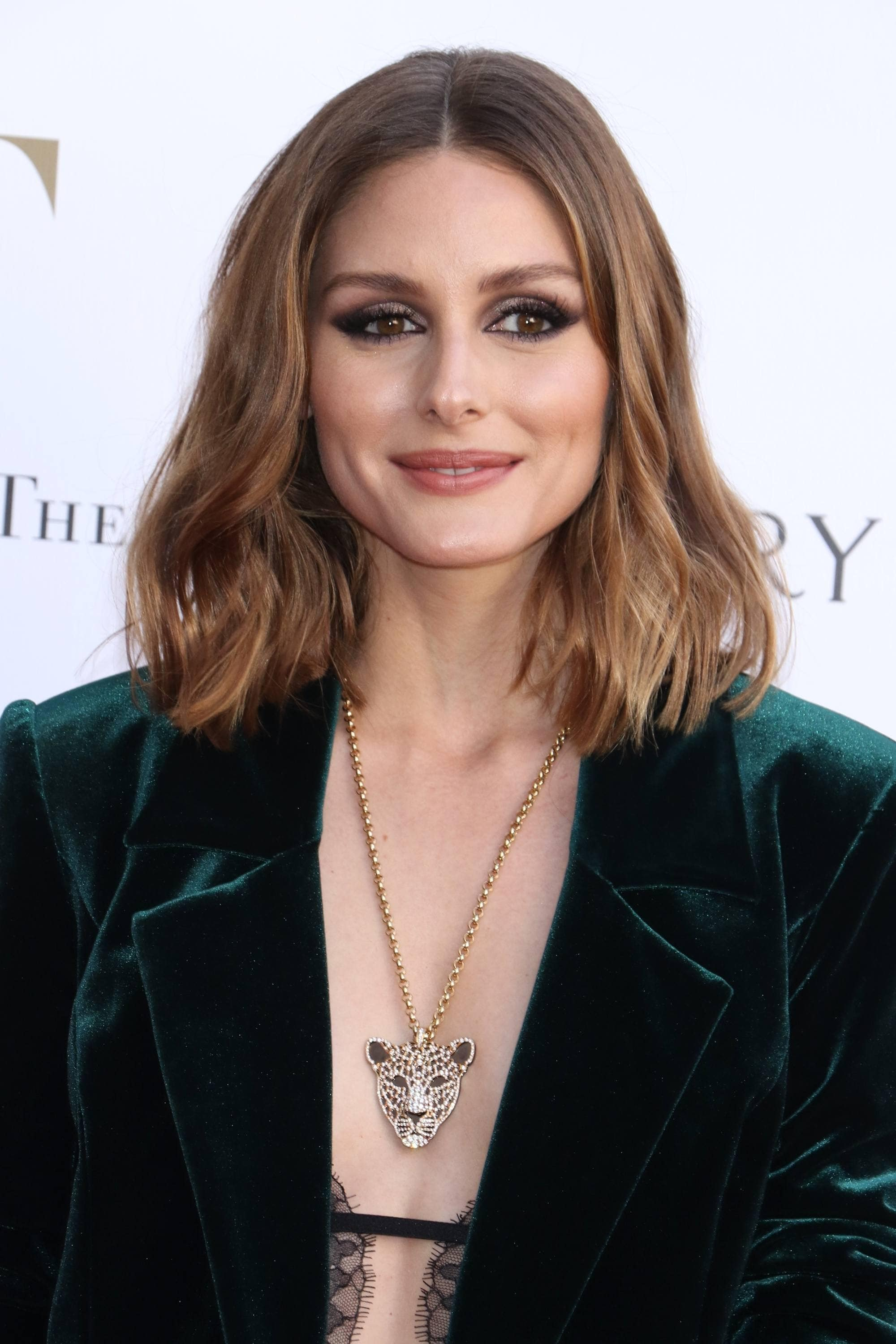 Medium hairstyles for thick hair: Olivia Palermo with mid-length light brown wavy hair, wearing a green velvet blazer