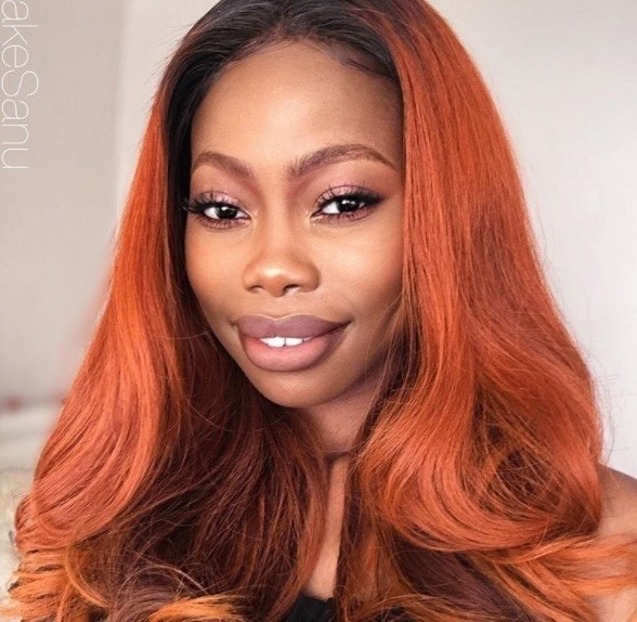 close up shot of woman with shiny pumpkin spice hair worn long and in loose waves at the end