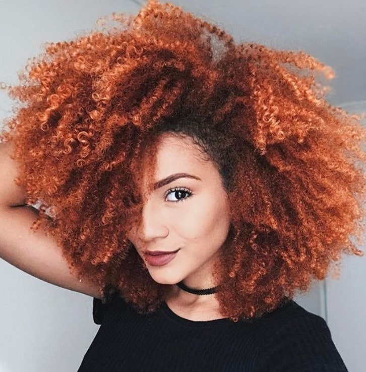 close up shot of woman with curly hair in a burnt orange colour