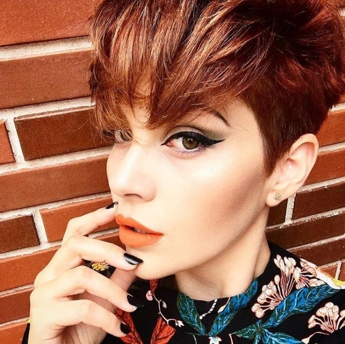 close up shot of woman with pumpkin spice hair colour with a pixie haircut
