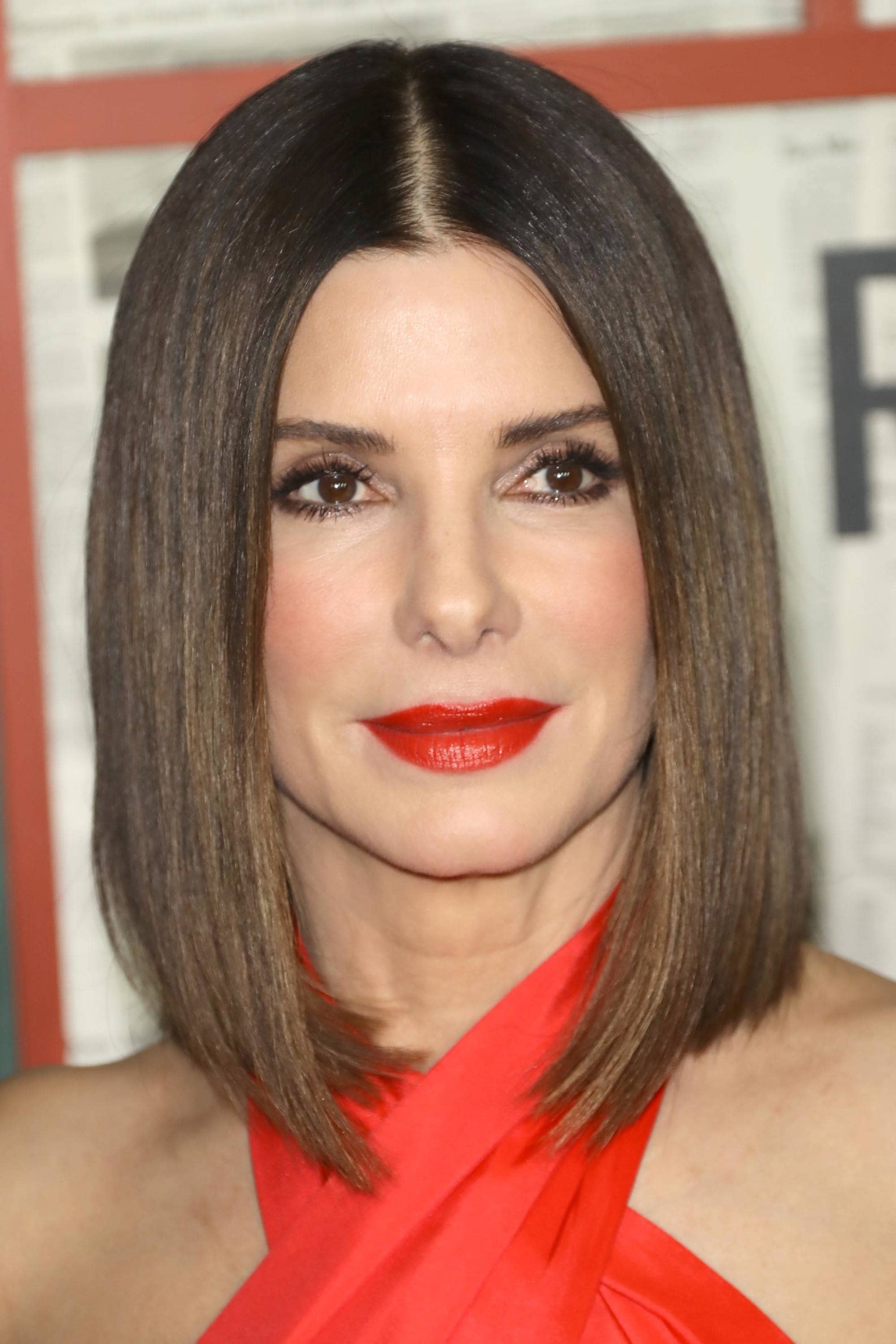 Medium hairstyles for thick hair: Sandra Bullock with a sleek straight A-line bob, wearing red lipstick and a red halterneck dress
