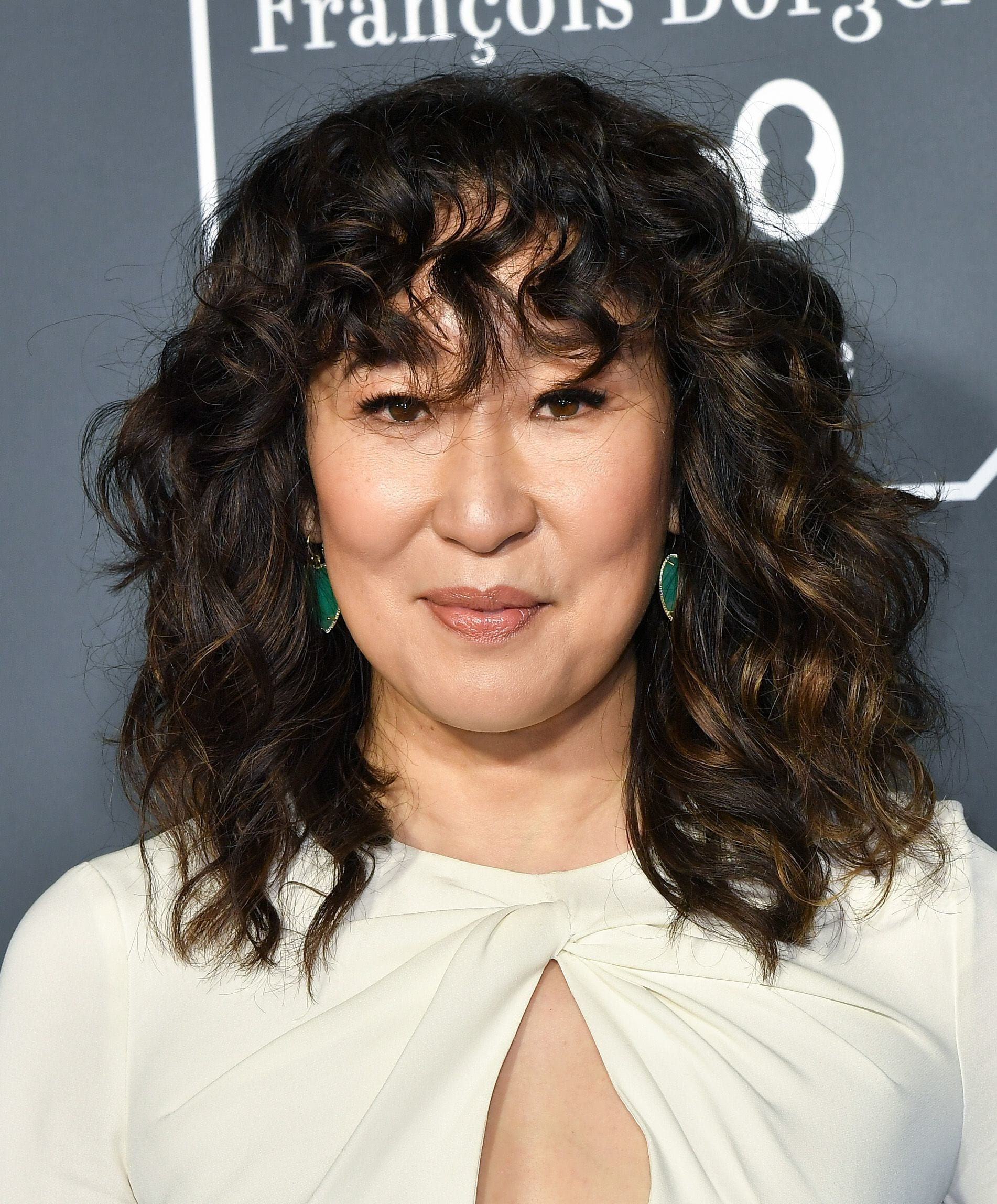 Medium hairstyles for thick hair: Sandra Oh with a dark brown curly shag
