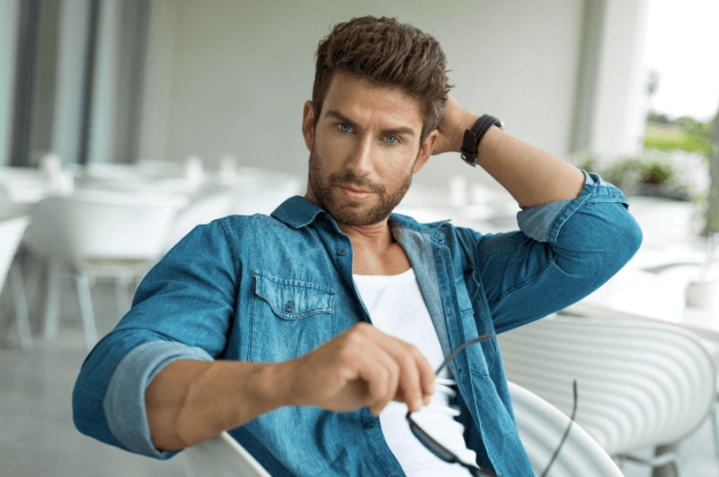 Men's haircuts for round faces: A man with medium brown hair with his hair styled into a modern quiff, wearing a denim blue jacket and posing in a sitting room