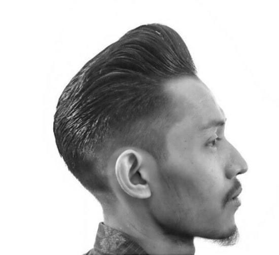 Men's haircuts for round faces: A man with a goatee beard and a slicked back dark brown pompadour hairstyle posing in a studio