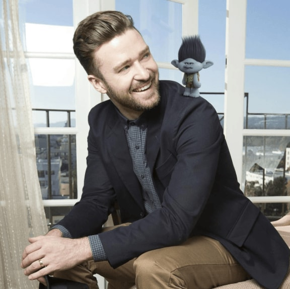 Men's haircuts for round faces: Justin Timberlake with a voluminous, swept-back hairstyle, wearing a black blazer, grey shirt and beige chinos