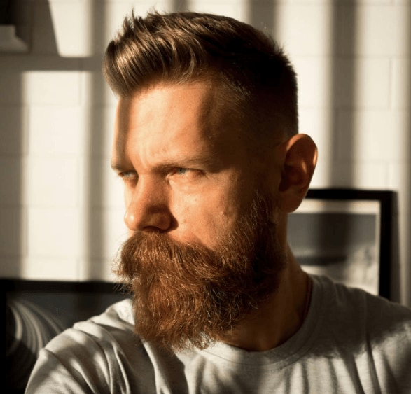 Men's haircuts for round faces: A man with ginger hair colour, with his hair styled into a vertical way with a full beard