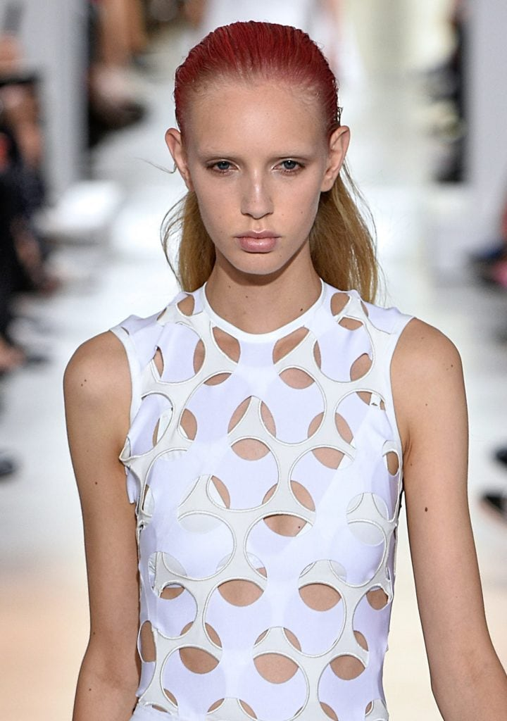 model on the Paco Rabanne SS17 runway wearing a white cut out dress with long blonde hair slicked back with a red colour spray coloured