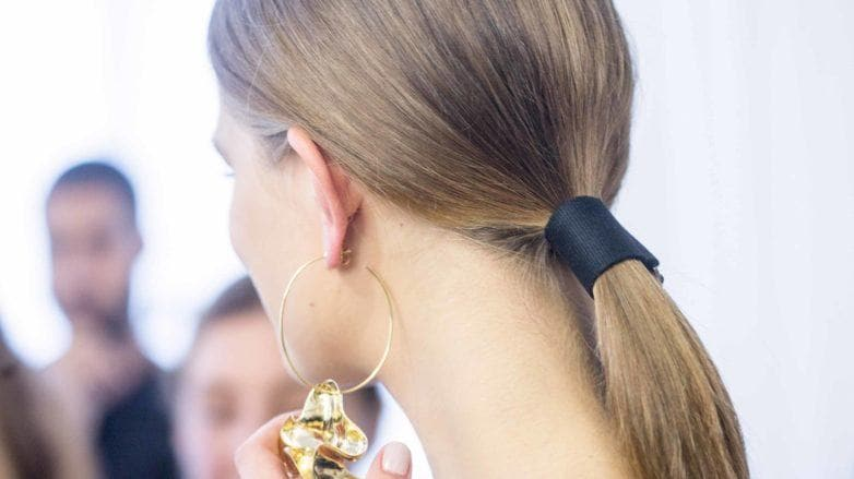 back view of a model with brunette hair worn in a low ponytail and a belted accessory at the Tibi SS17 show wearing a pair of large hooped earrings