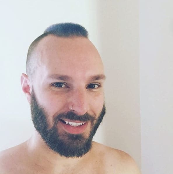 Dark haired man with beard and subtle, barely-there mohawk