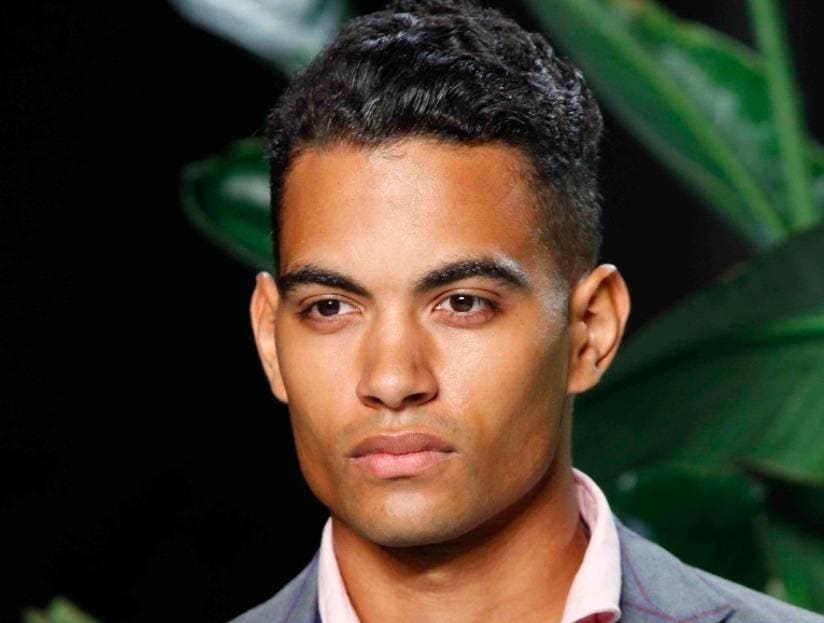front view of a man with wavy black hair and an undercut