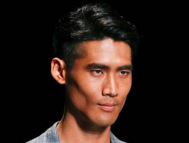 front view image of a man with black hair and an undercut with a side parting