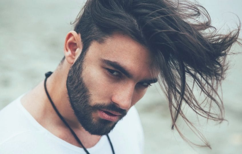 front view of a man with dark hair and a long undercut