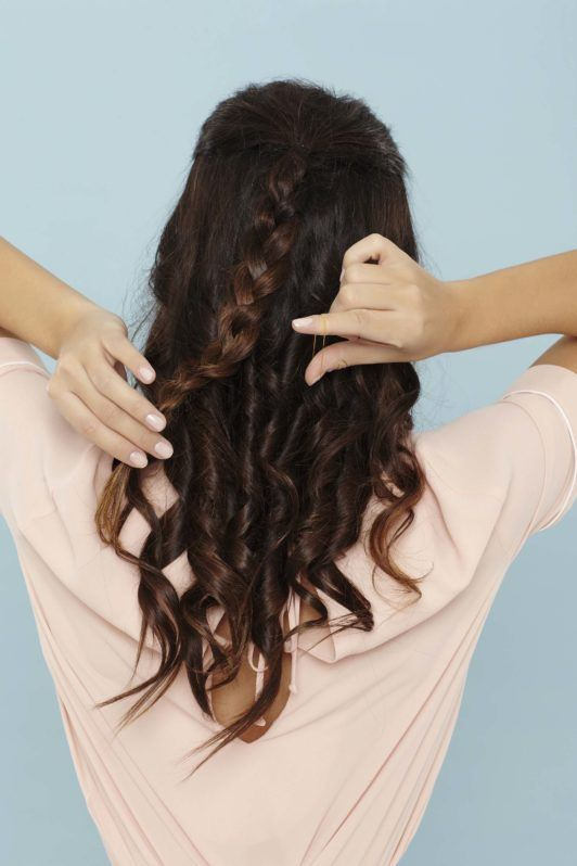 back shot of a woman with long brunette hair braiding her hair