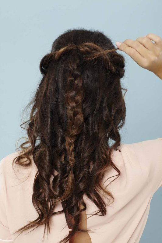 back shot of a woman with long brunette hair adding extra hair into her braid