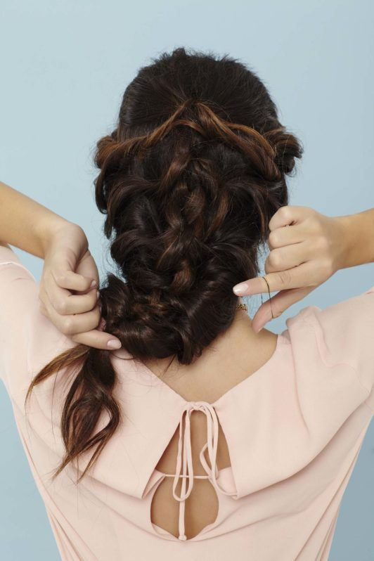back shot of a woman with long brunette hair securing her braid with a hairband