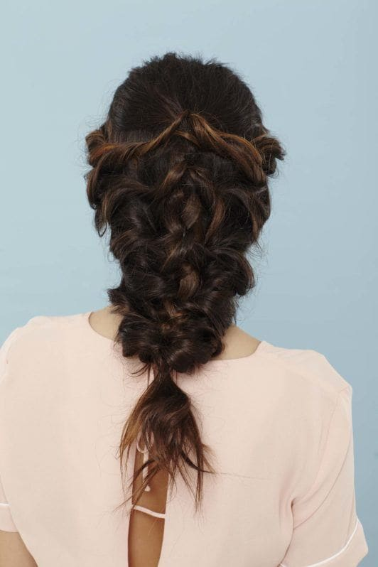back shot of a woman with long brunette in a mermaid braid wearing a pink top