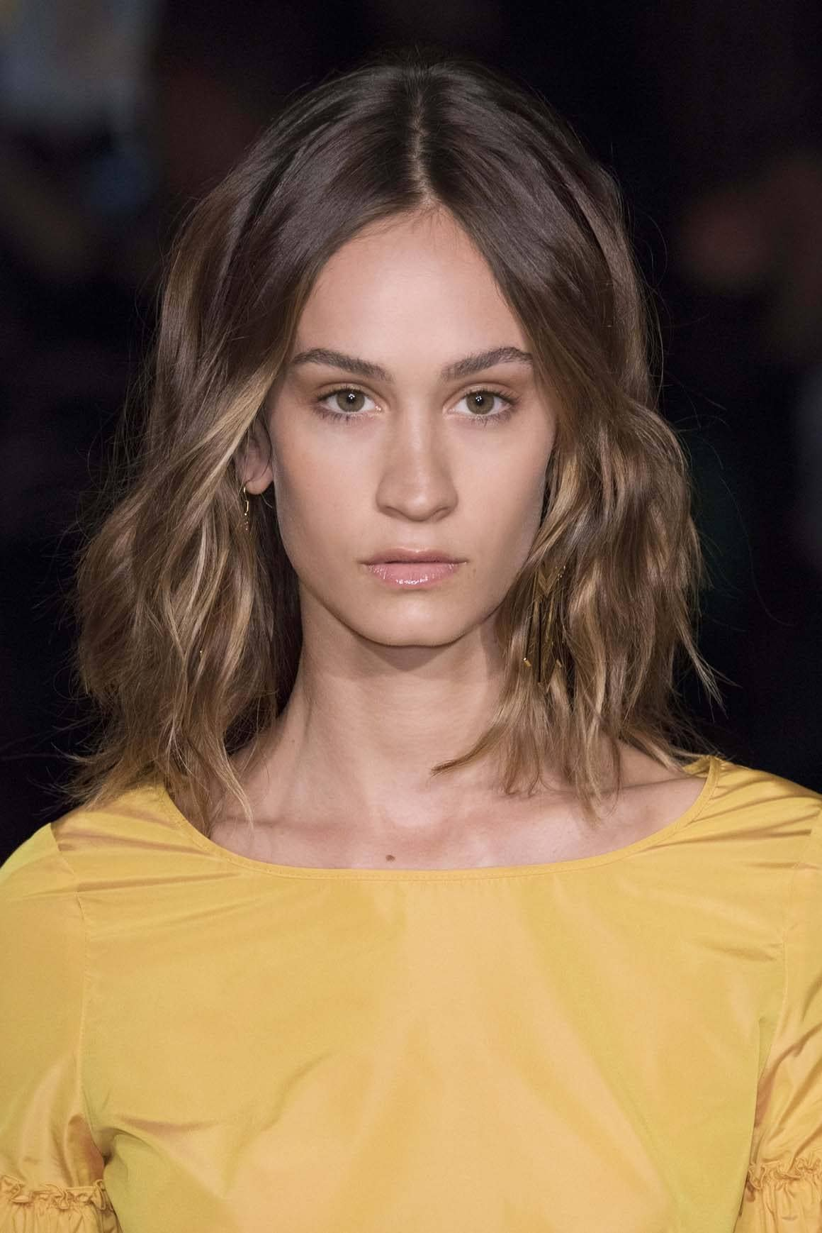 Medium hairstyles for thick hair: Brunette model with wavy mid-length hair with fluffed-out ends