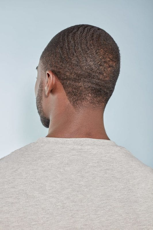 360 waves: Back view of a man with short afro hair styled in 360 waves