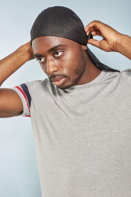 360 waves: Man tying a black silky durag around his short afro hair, wearing a grey t-shirt