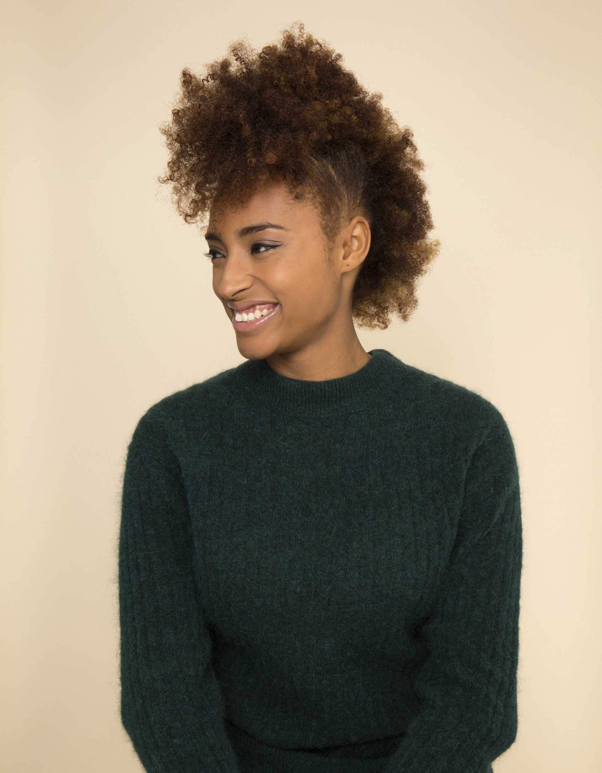 Black history month hair: Close up shot of a woman with natural honey brown afro hair styled into a 'frohawk, wearing green jumper and earrings, posing in a studio