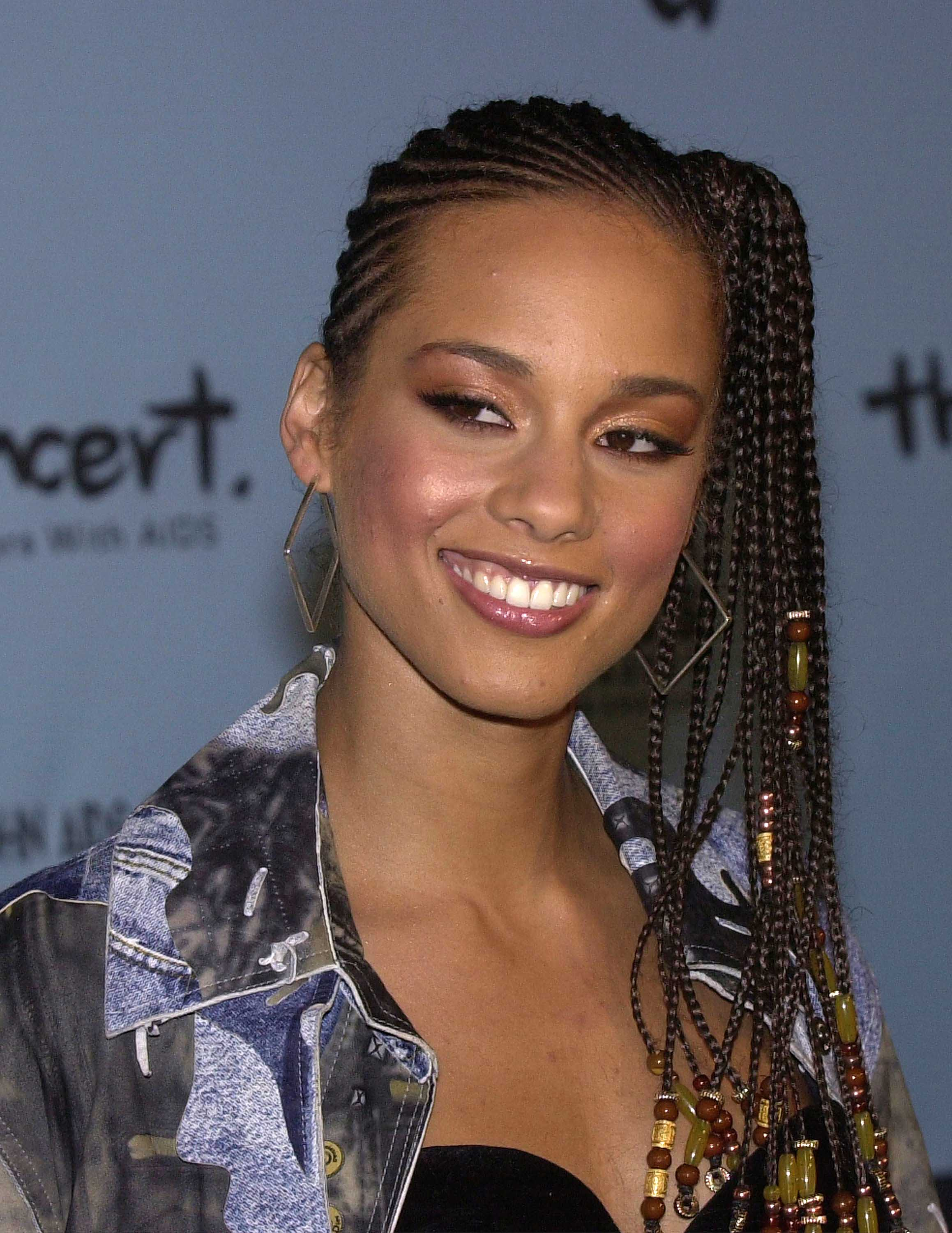 Black history month hairstyles: Close up of Alicia Keys with side cornrows styled into a side ponytail, wearing denim jacket and posing on the red carpet