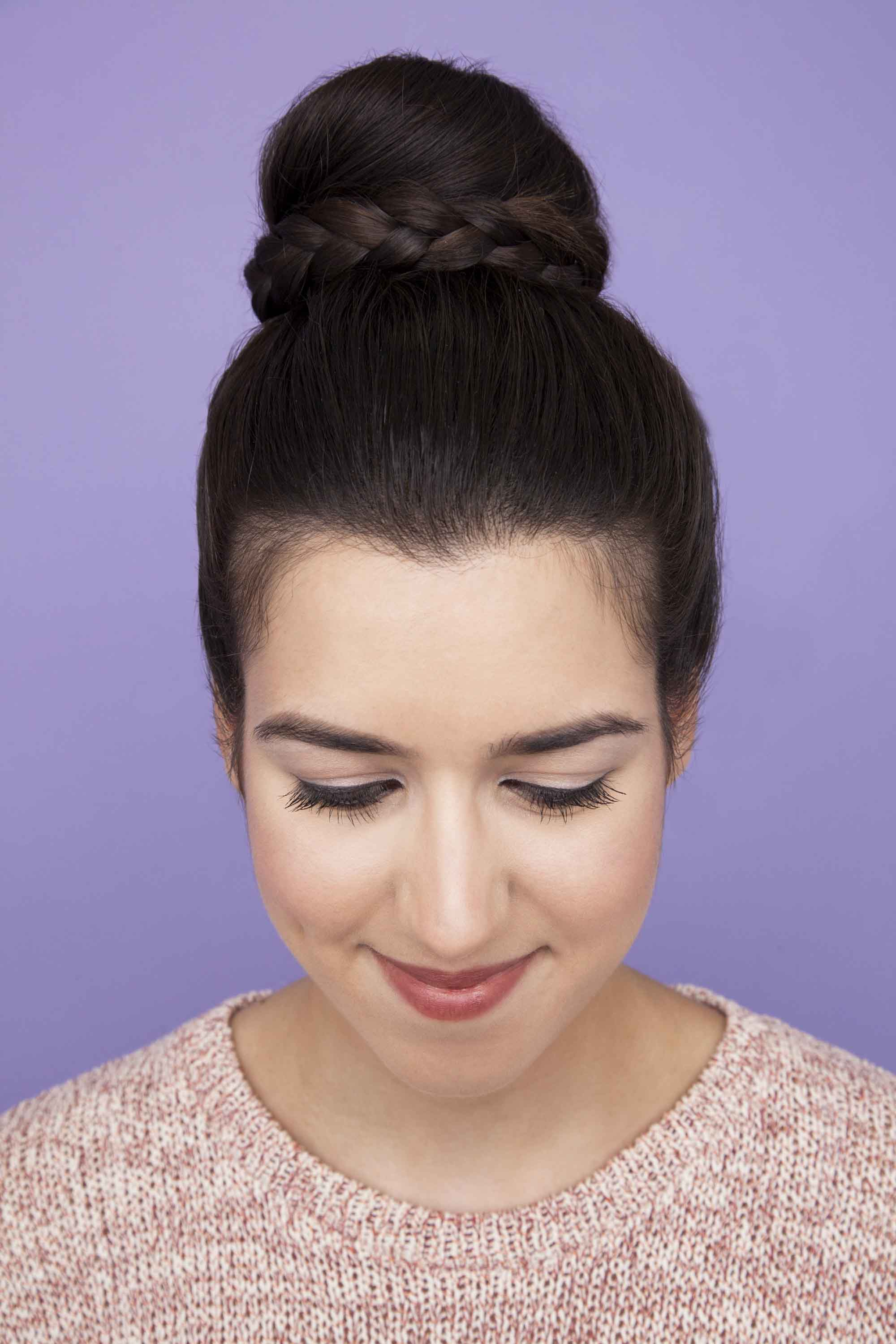Easy updos - Braided ballerina bun on dark-haired model against a purple backdrop