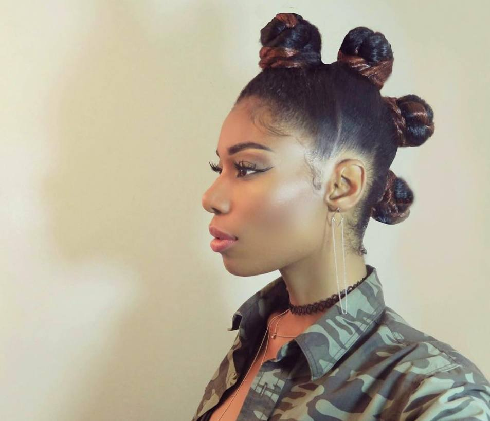 Black History Month hair: Close up shot of a woman with braided dark brown bantu knots styled into a mohawk, wearing a camouflage jacket with orange top and necklace