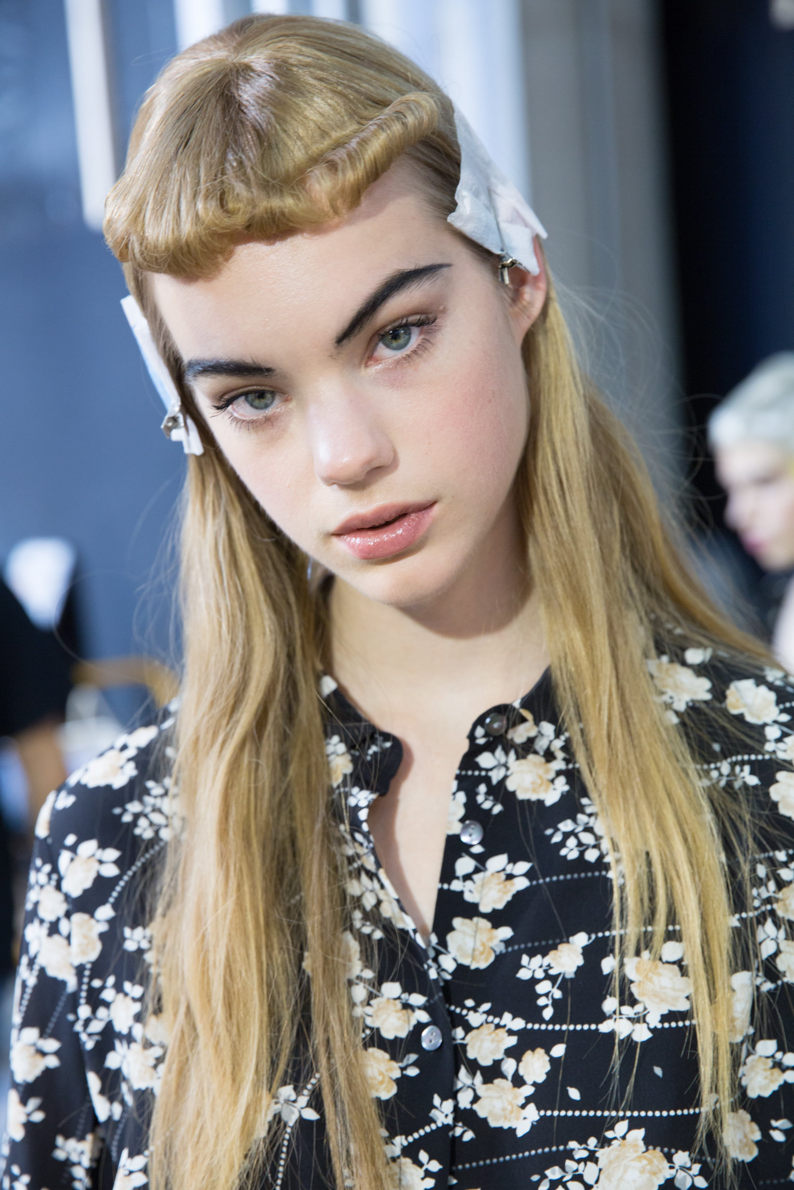Short bangs: Blonde model with long hair and retro rolled micro short fringe backstage at fashion show.