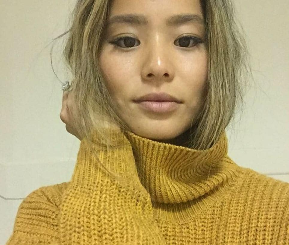 actress Jamie Chung taking a selfie wearing a chunky yellow turtle neck sweater with ash blonde hair tucked inside