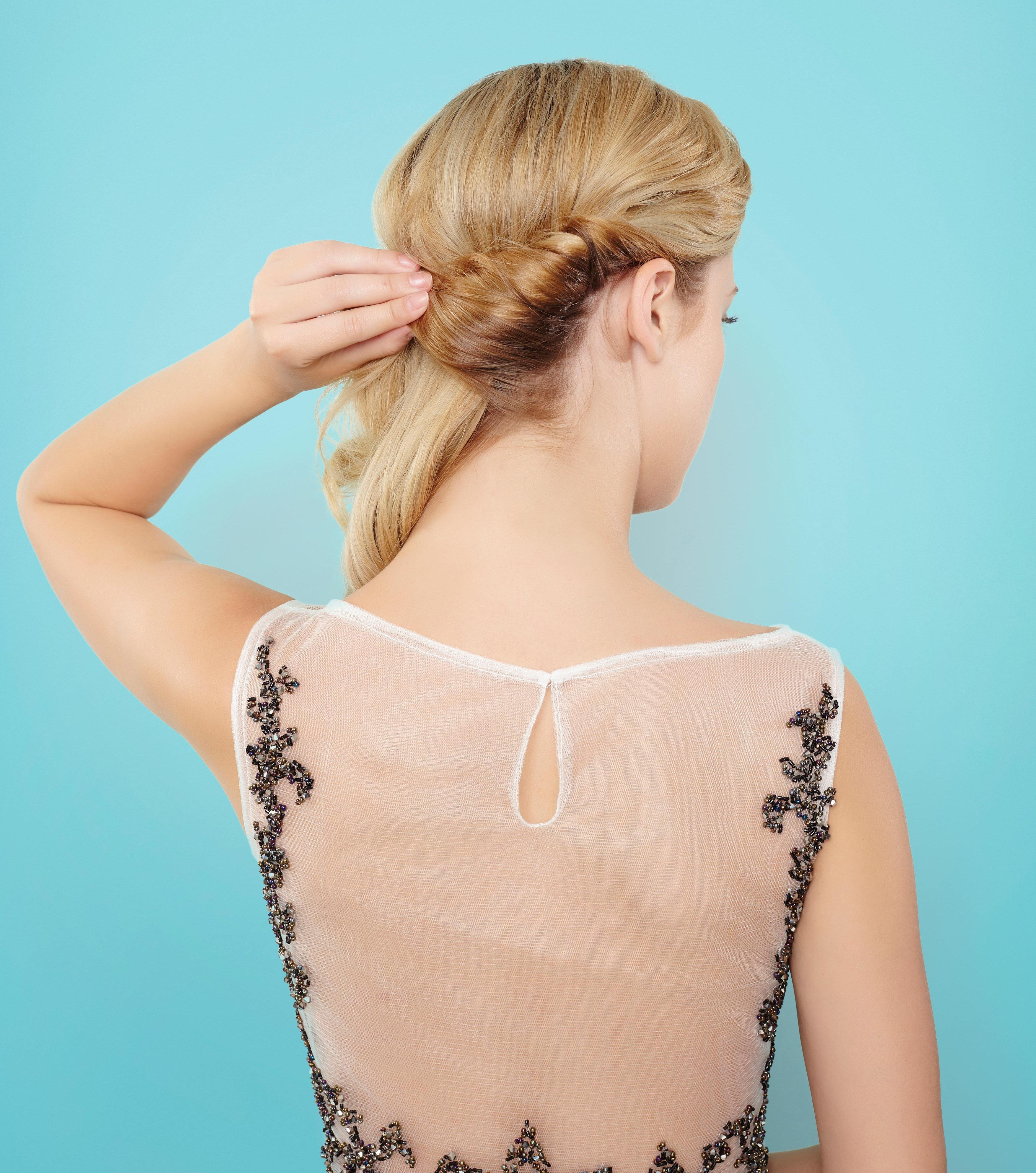 back view of a blonde model twisting a section of her hair into a croissant bun